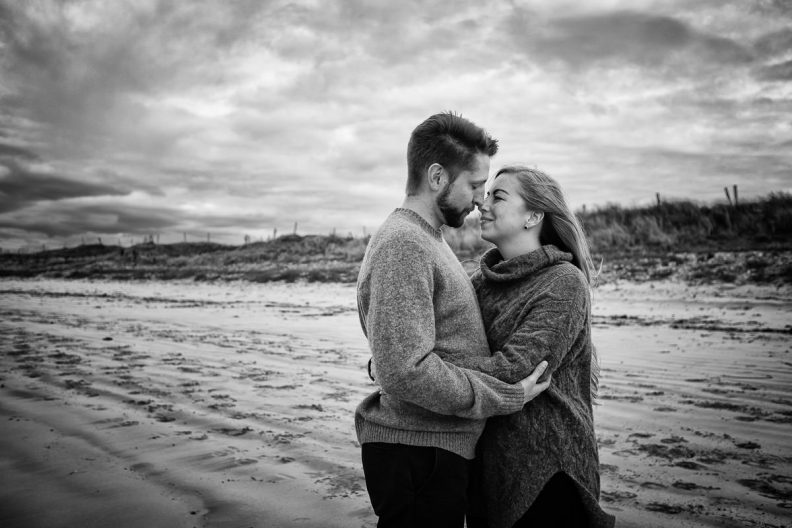 engaged couple on a beach in wild atlantic way ireland