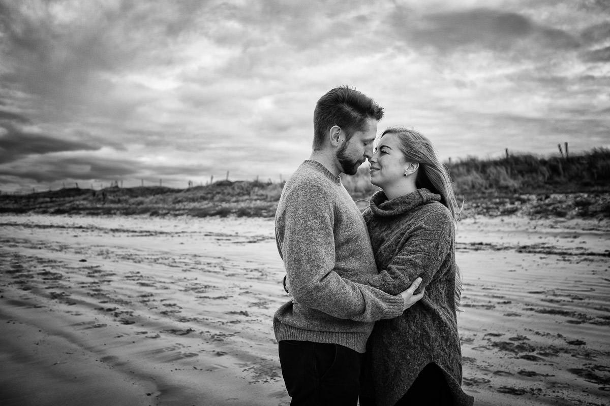 engaged couple on a beach in wild atlantic way ireland