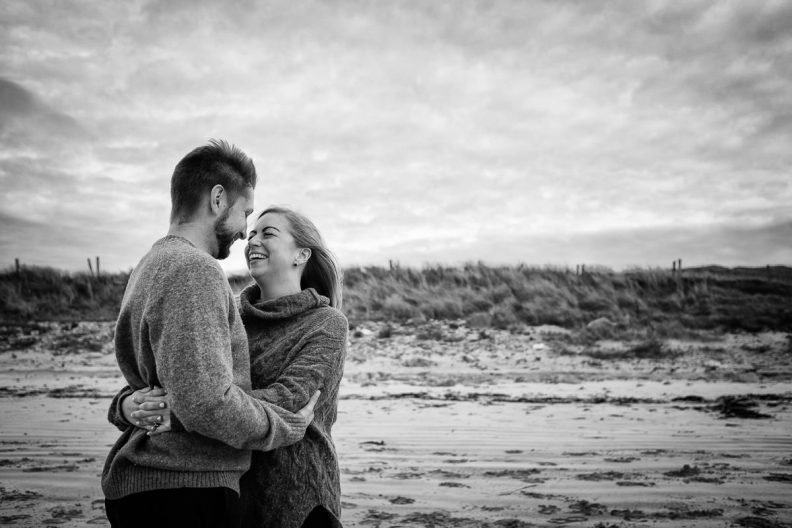 engaged couple laughing on a beach in wild atlantic way ireland