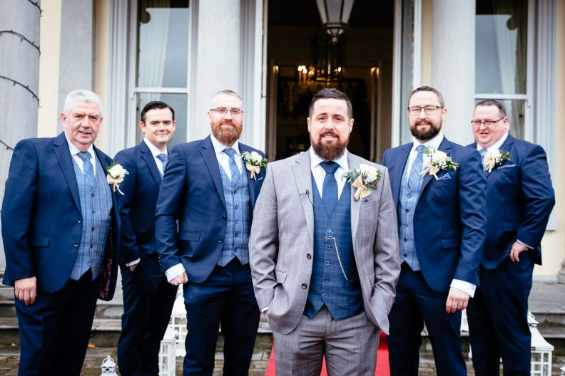 groom and groomsmen standing in front of balyna house
