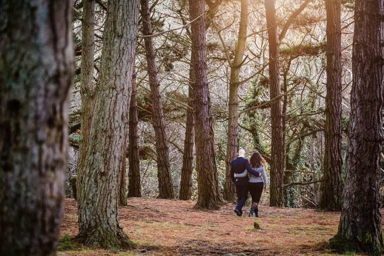 engaged couple walking in forest at sun set