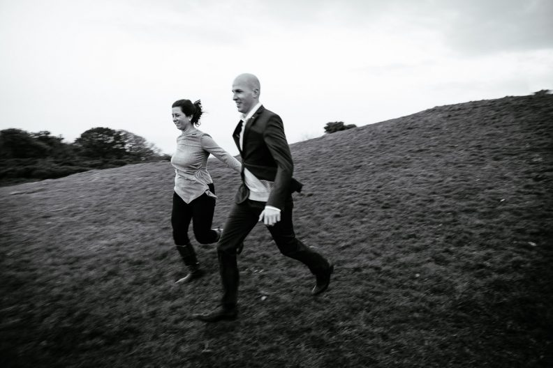 engaged couple running down a hill
