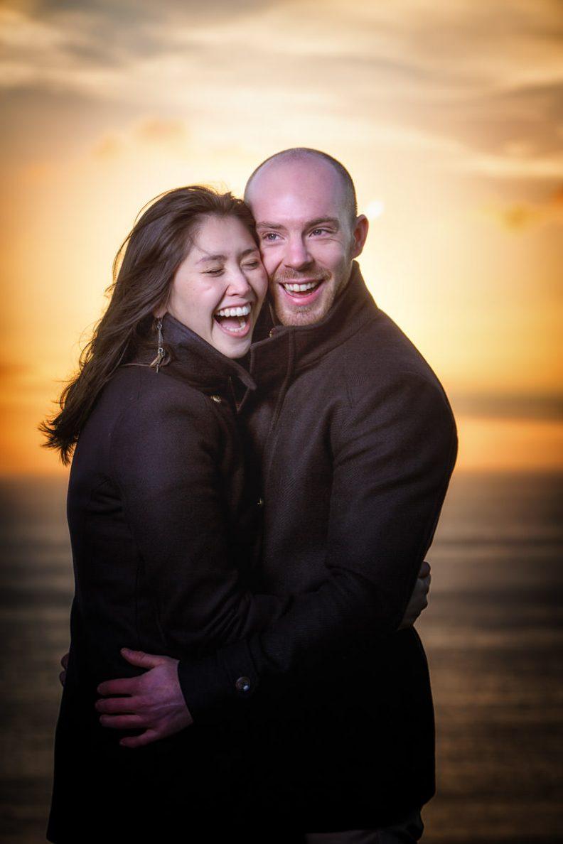 engaged couple laughing at sunrise