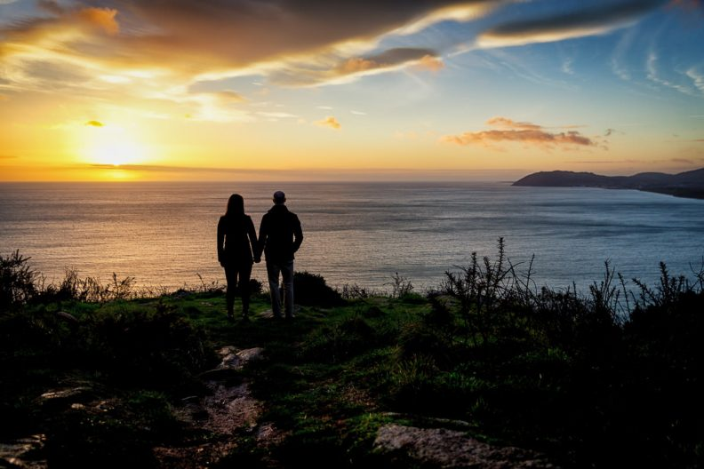 engaged couple looking out over sea at sunrise