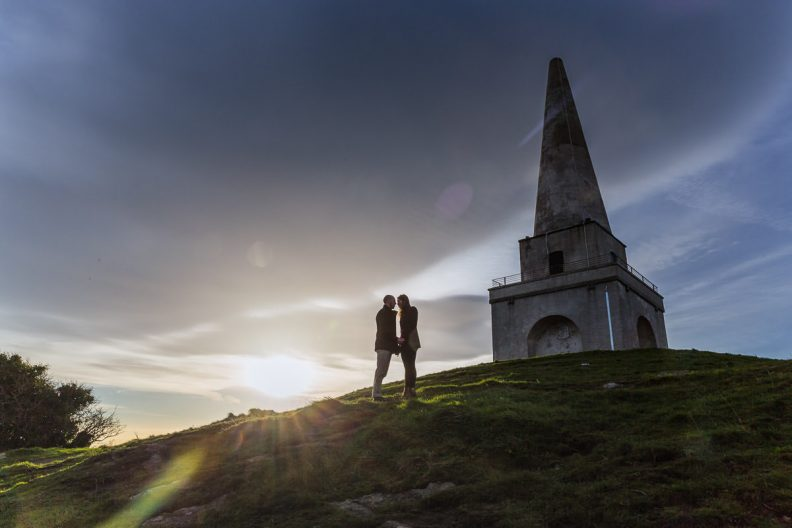 engaged couple walking up a hill