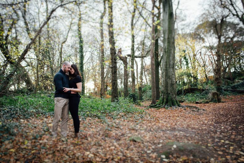 engaged couple embracing in forest