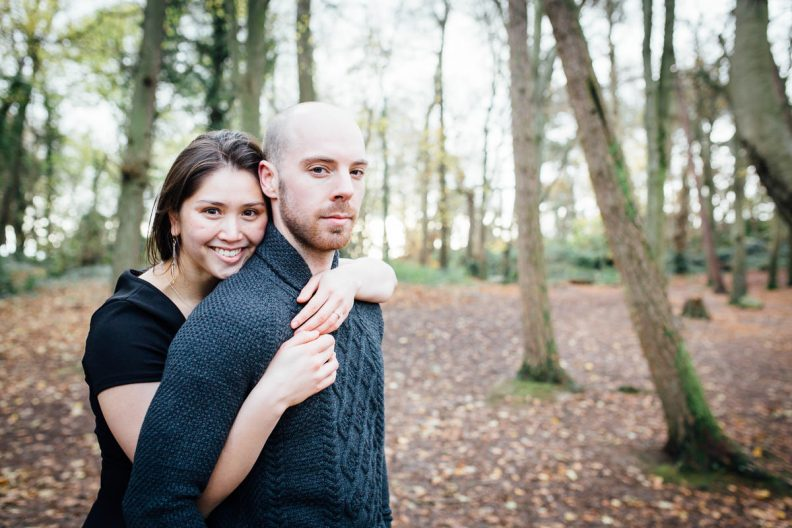 engaged couple posing for a photo in forest