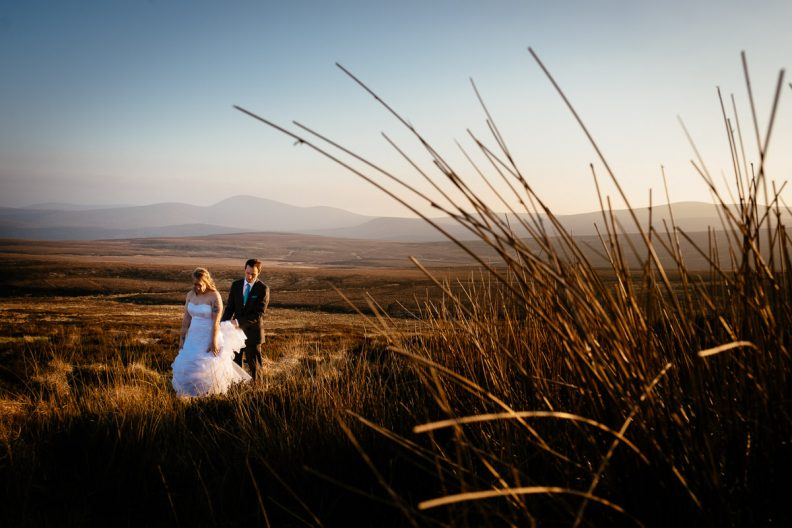 bride and groom walking through a meadow at sunset