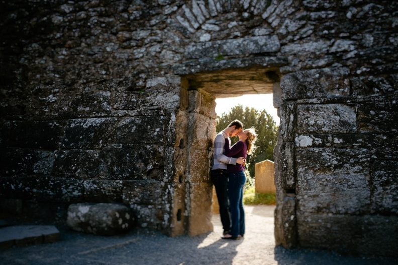 engaged couple at doorway to old church