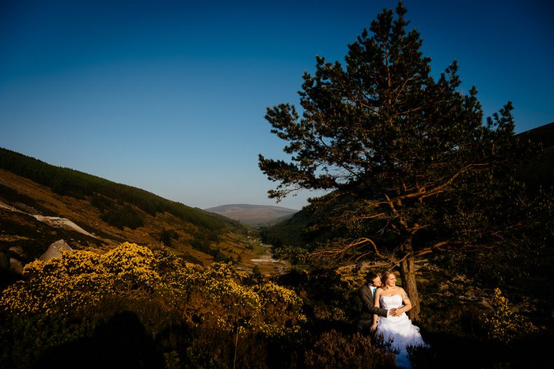 bride and groom standing on a mountain at sunset