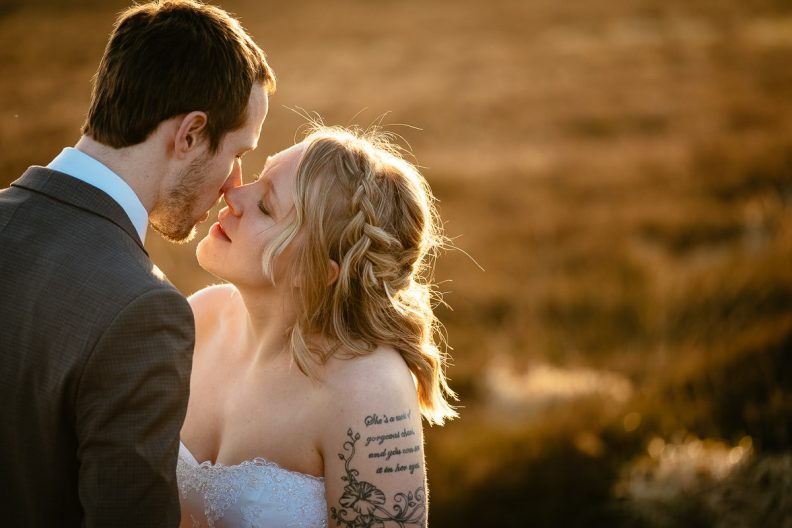 bride and groom kissing on a mountain at sunset