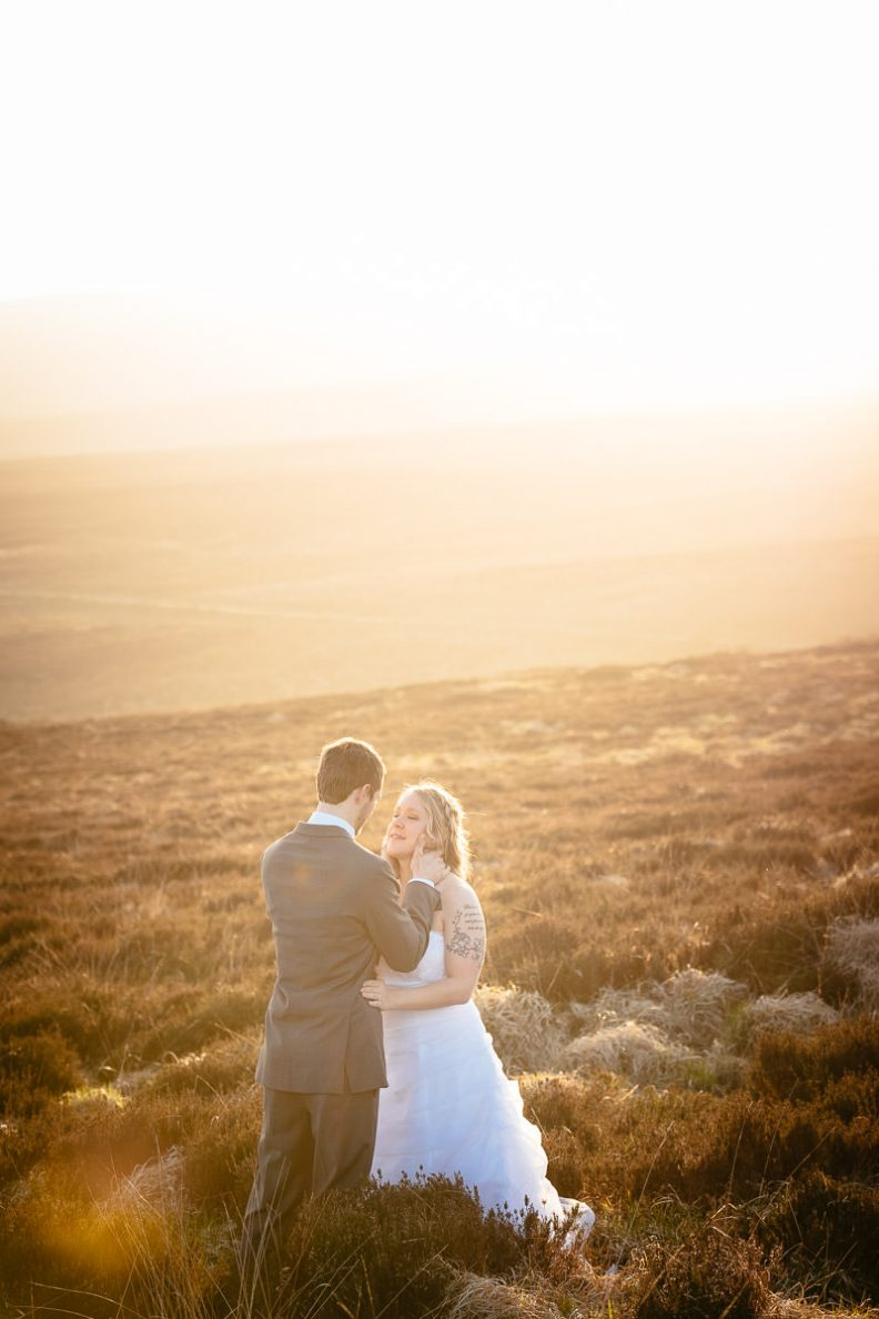 bride and groom walking on a mountain at sunset