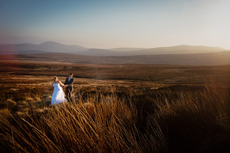 bride and groom walking on a open plain at sunset