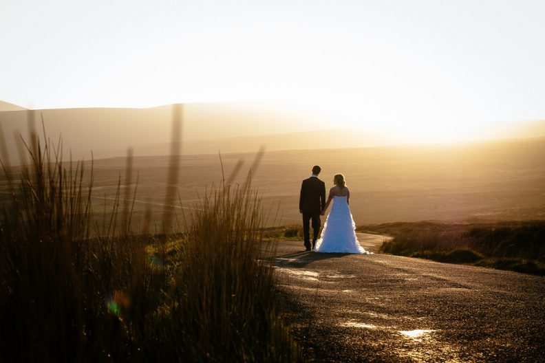bride and groom walking on a empty road at sunset