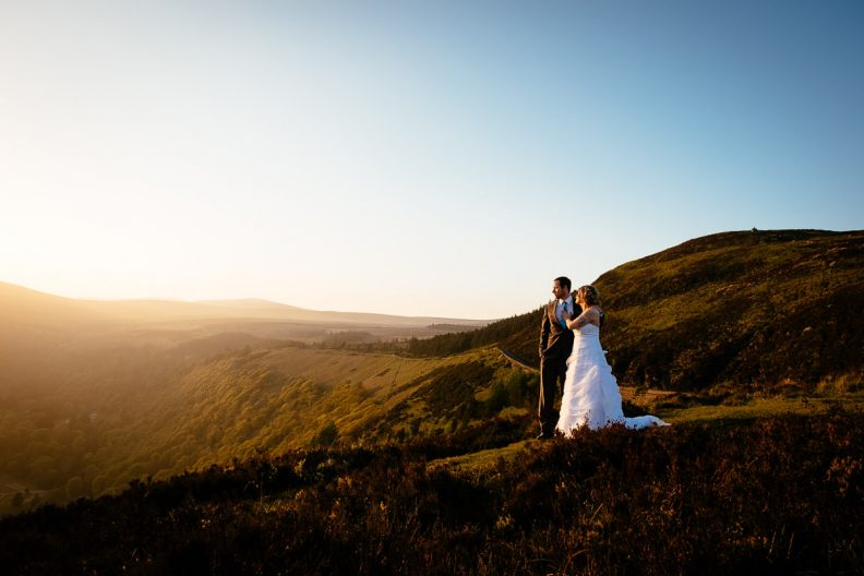 bride and groom hugging by lough tay at sunset