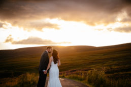 bride and groom walking towards the sunset in Irish mountains
