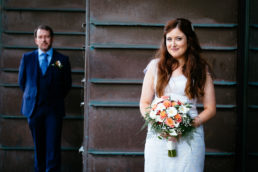 bride looking at camera with groom standing behind at university college cork wedding