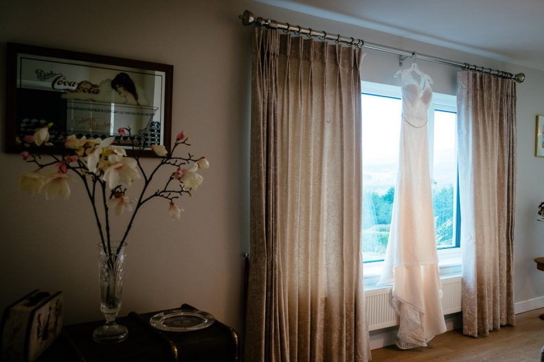 wedding dress hanging at window