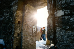 engaged couple standing outside church in winter sunshine