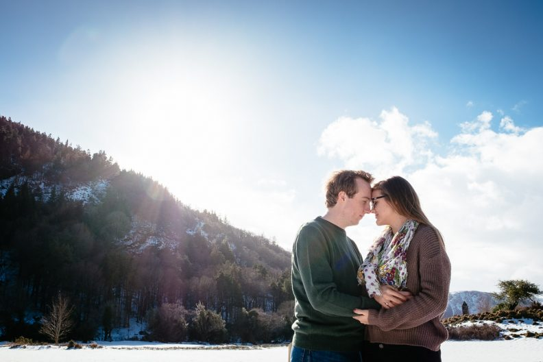 engaged couple embracing in snow at glendalough