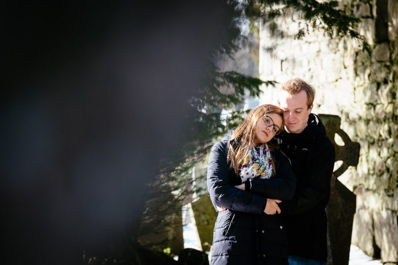 engaged couple hugging in snow at glendalough