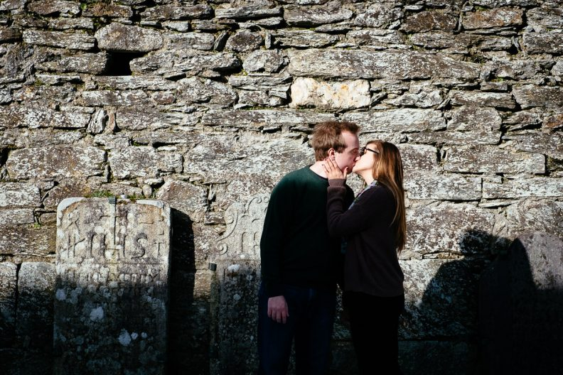 engaged couple kissing in snow at glendalough