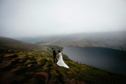 bride and groom walking across mountain in Wicklow, Ireland