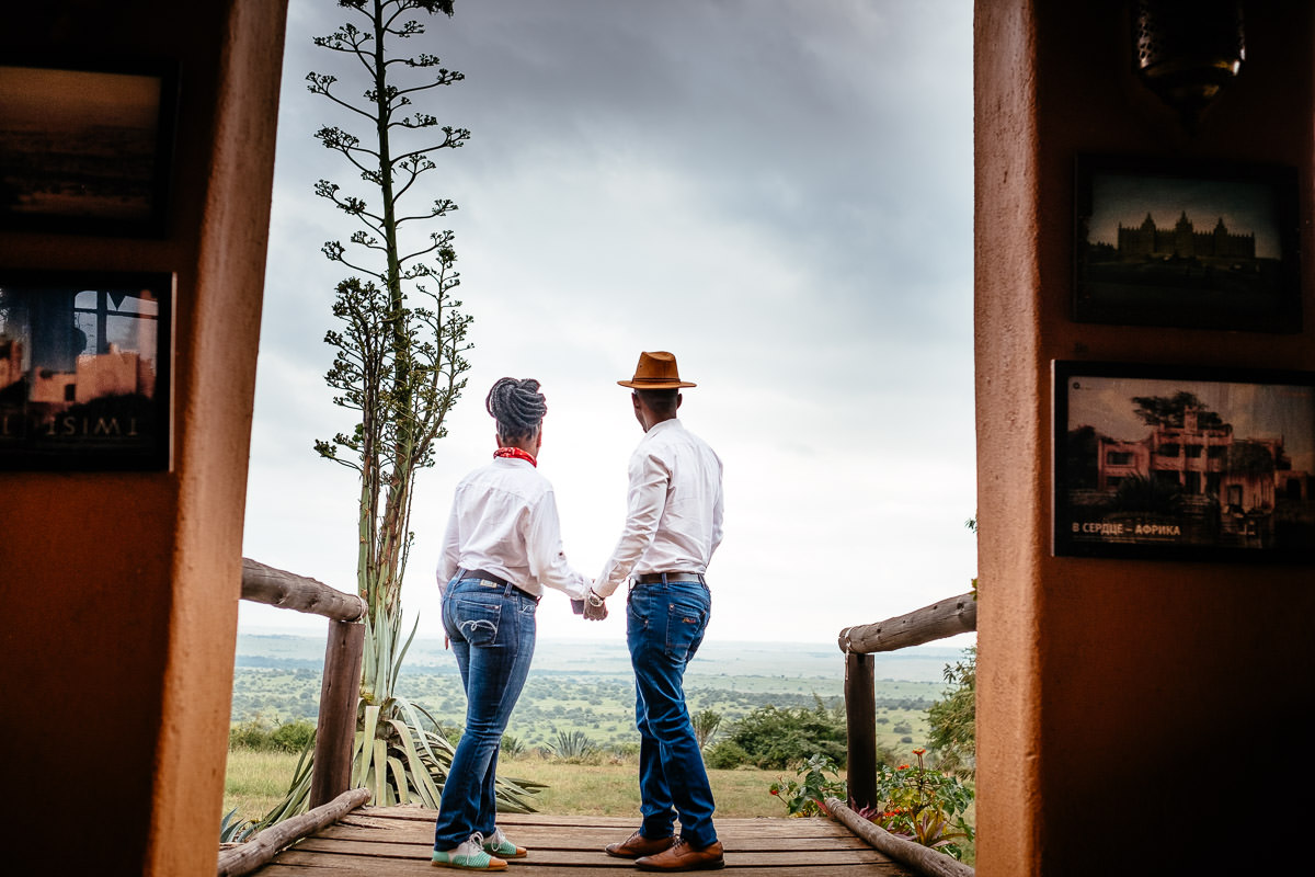 engaged couple looking out over the savanna kenya