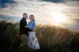 engaged couple in long grass at sunset in dublin