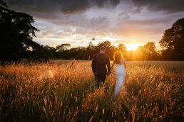 bride and groom walking through field of wheat in Ireland towards a setting sun
