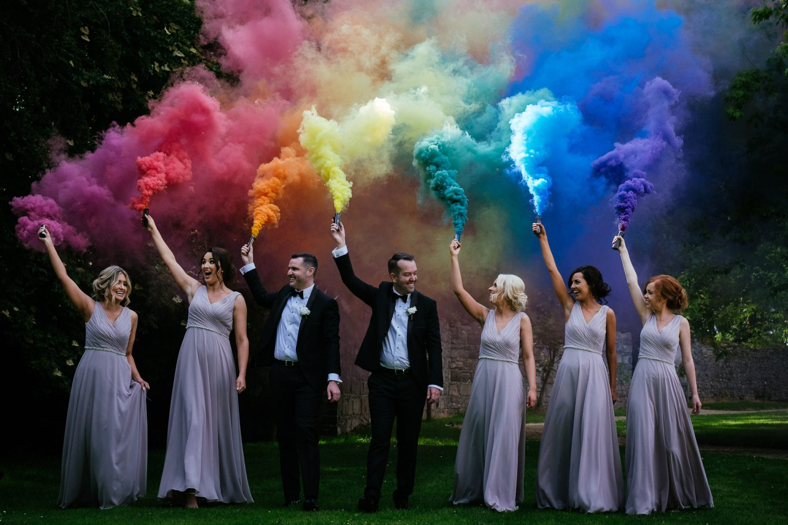 two gay grooms and bridesmaids holding smoke bombs