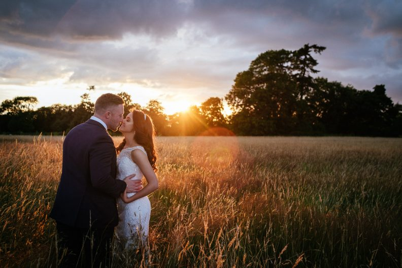 bride and groom kissing in a field of wheat with the sun setting behind them