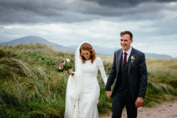 bride and groom laughing and walking along beach in west of ireland with mountains in background