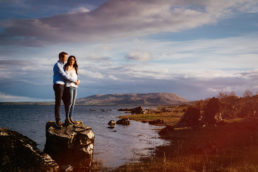 future bride and groom standing on a rock by a lake in rural ireland
