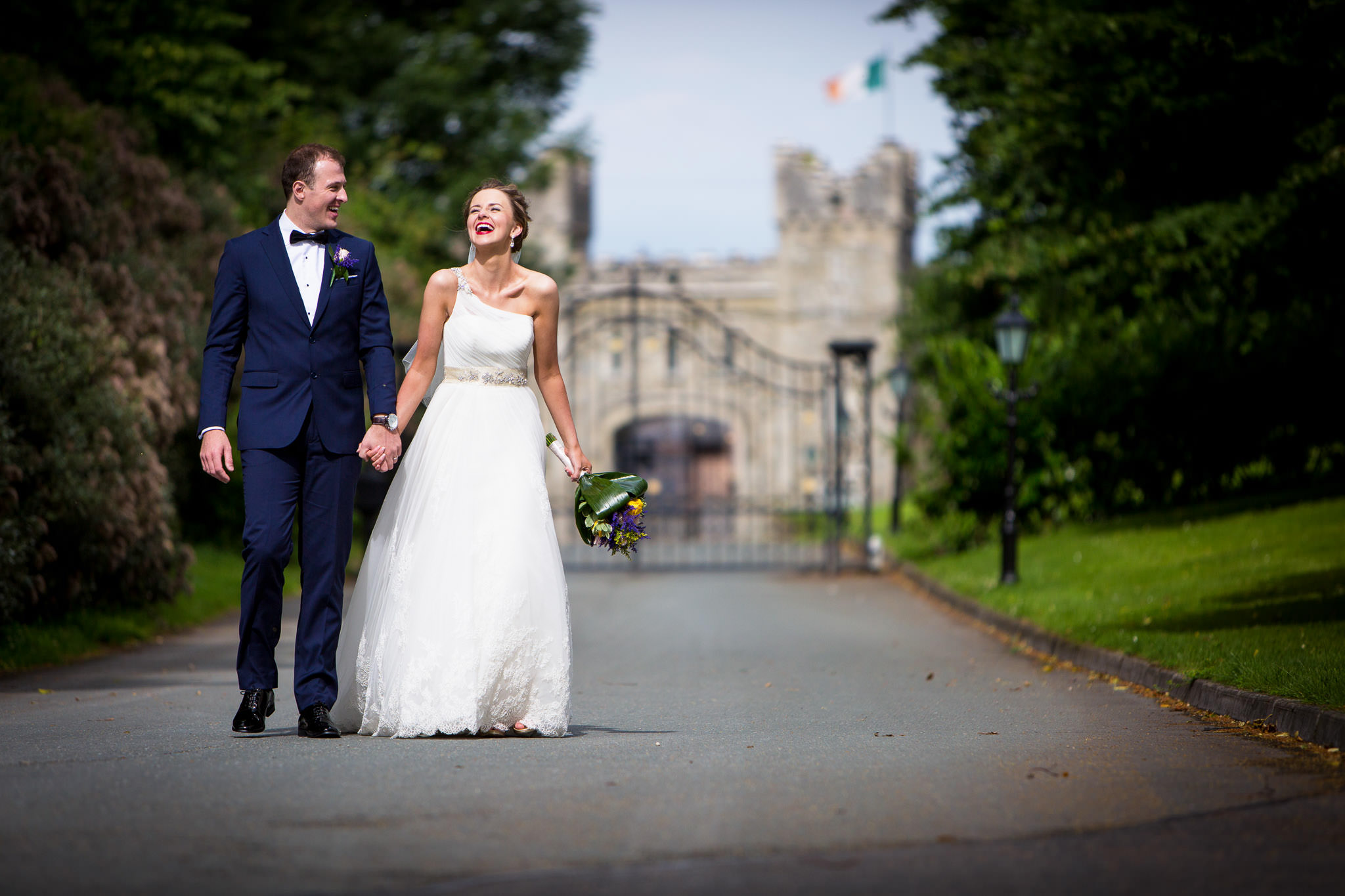 bride and groom walking down a road laughing wiht a castle in the background