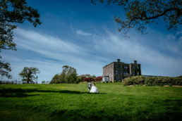 bride and groom walking through field in fron of horetown house in wexford