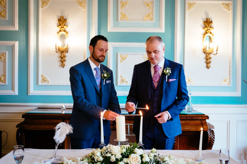 two grooms lighting candles at their irish gay wedding