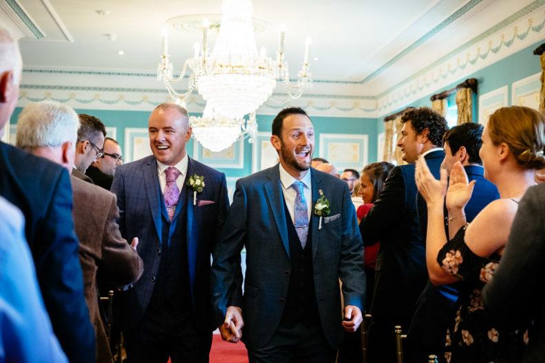 two grooms walking down aisle at their irish gay wedding