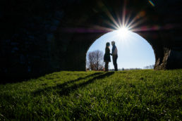 engaged couple standing under castle arch with sun filtering through creating sunflare