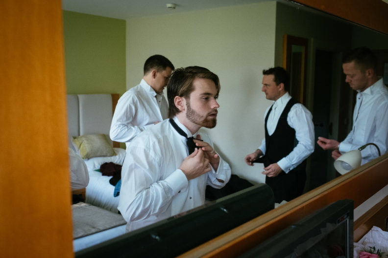 groomsmen getting ready in hotel room