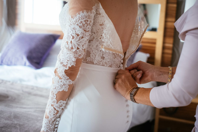 brides mother fastening button on back of wedding dress