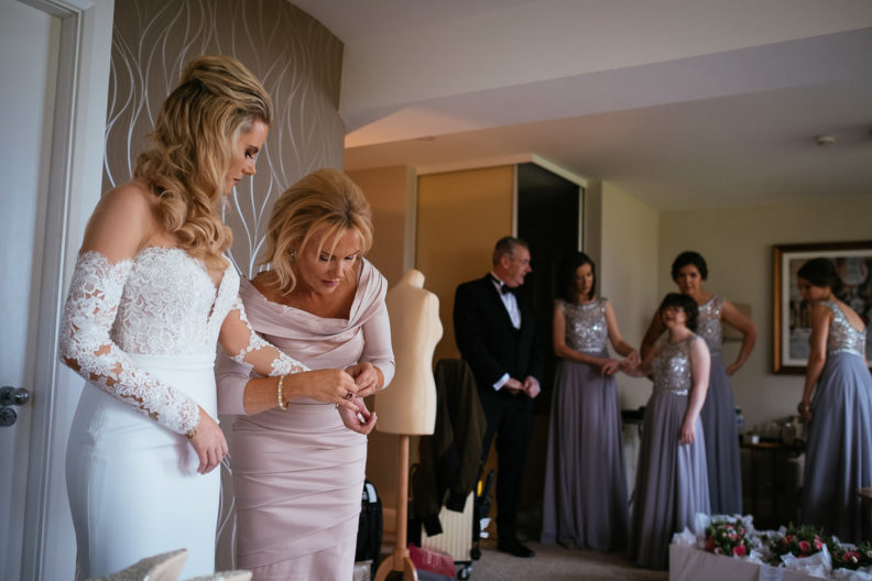 brides mother helping bride get dressed