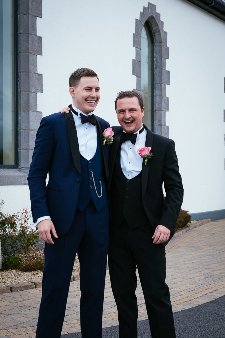 groom and best man laughing outside church