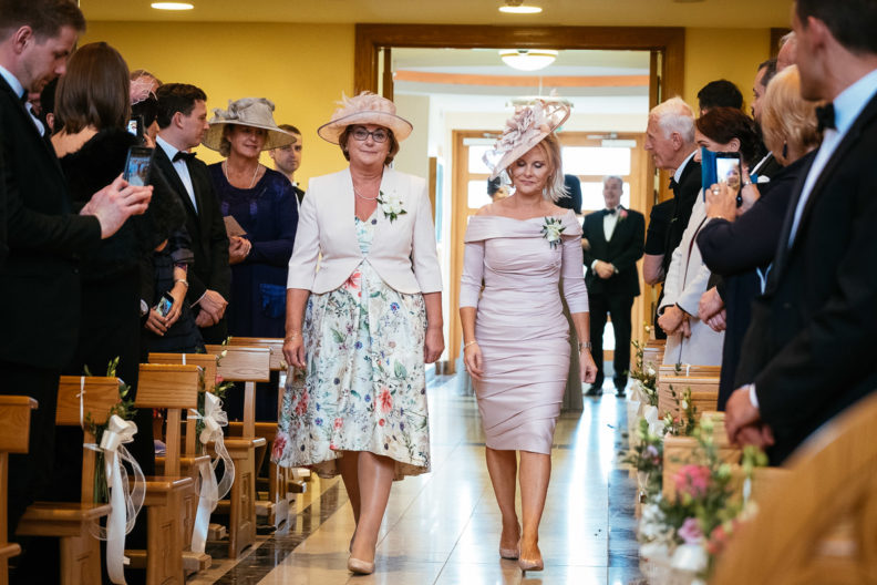two mothers walking up church aisle