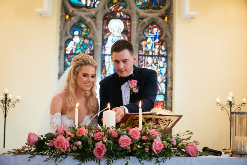 bride and groom lighting a candle