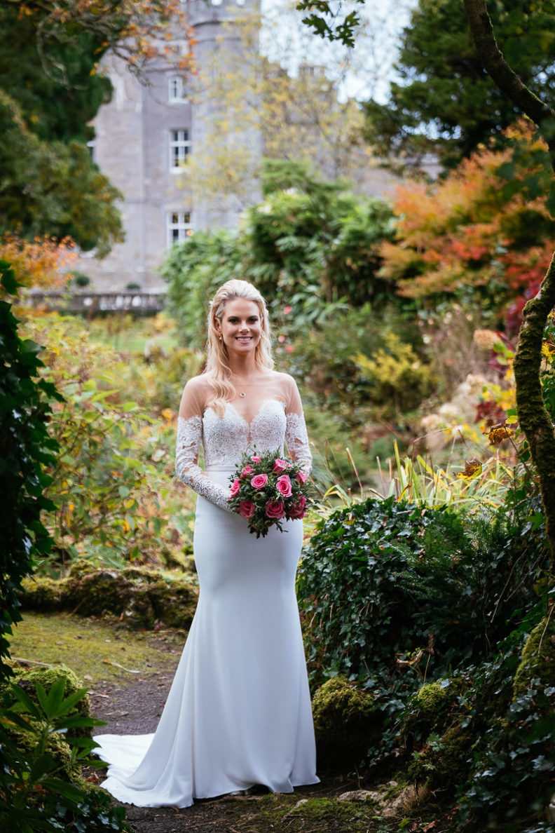 full length shot of bride in garden holding flowers
