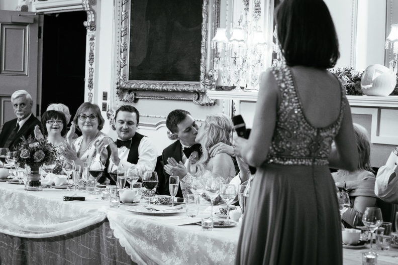 bride and groom kissing at dinner table during wedding dinner speeches