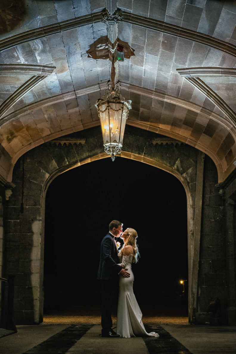 bride and groom kissing under lantern at night