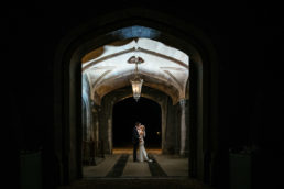 bride and groom standing under entrance hallway of markree castle at nighttime