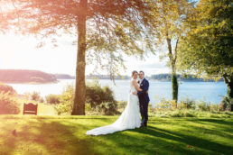 bride and groom standing in front of a lake on a golf course at tulfarris in wicklow withthe sun setting behind them